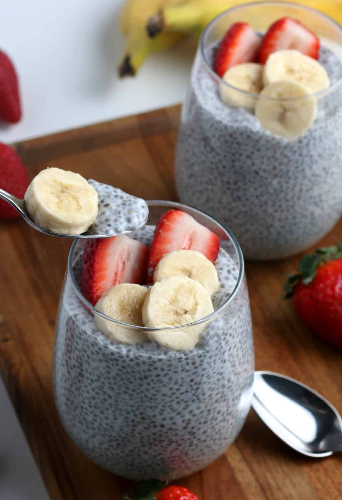 A spoon is dipping out a spoonful of vanilla chia pudding.