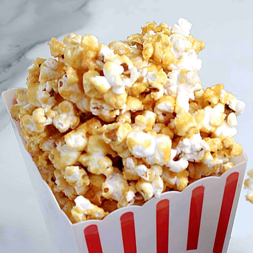 Closeup of vegan popcorn at the top of a red and white box.