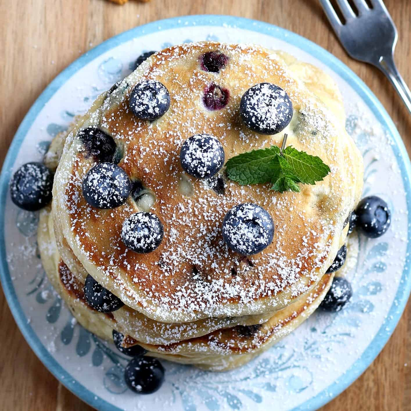Overhead view of a stack of pancakes covered with blueberries and powdered sugar.