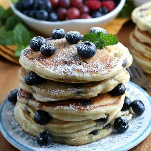 Stack of four pancakes showing blueberries and sprinkled with powdered sugar.