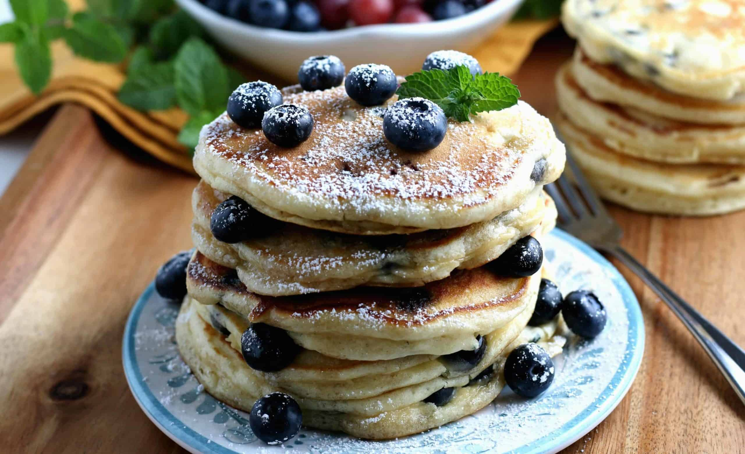 Wide photo of a stack of sugar frosted breakfast on a blue plate.