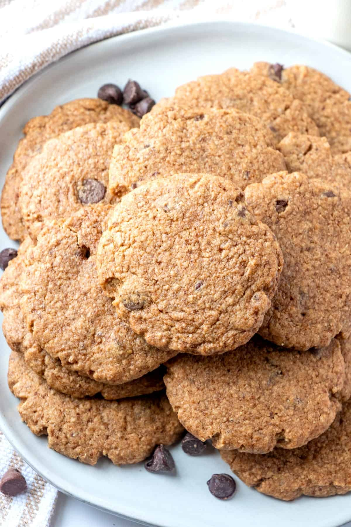 Angled view of a pile of baked peanut butter vegan cookies on a white plate.