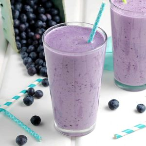 Glasses with fruit smoothie with fresh blueberries behind.