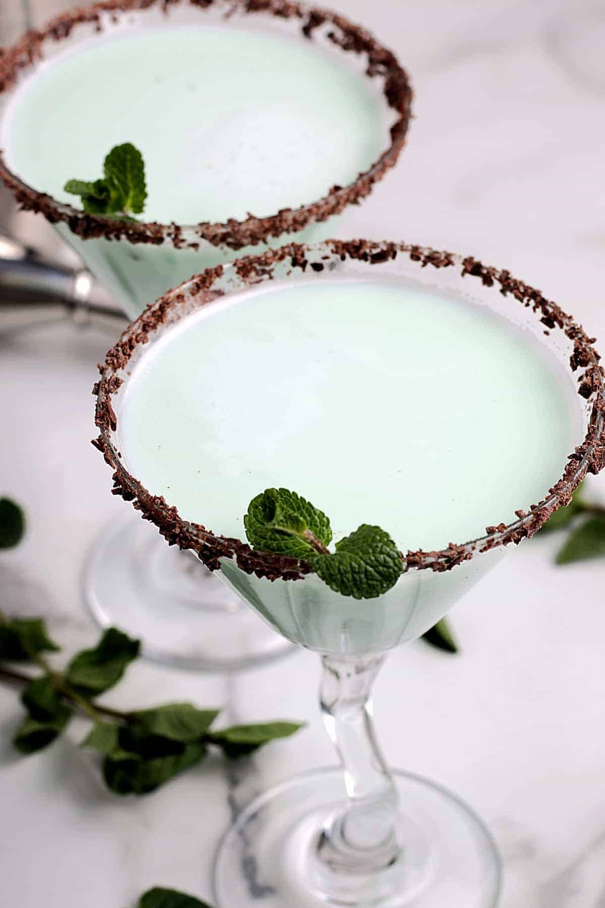 Two glasses filled with a grasshopper drink and a chocolate rim.