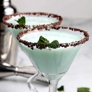 Two stemmed glasses filled with a frothy mint green cocktail