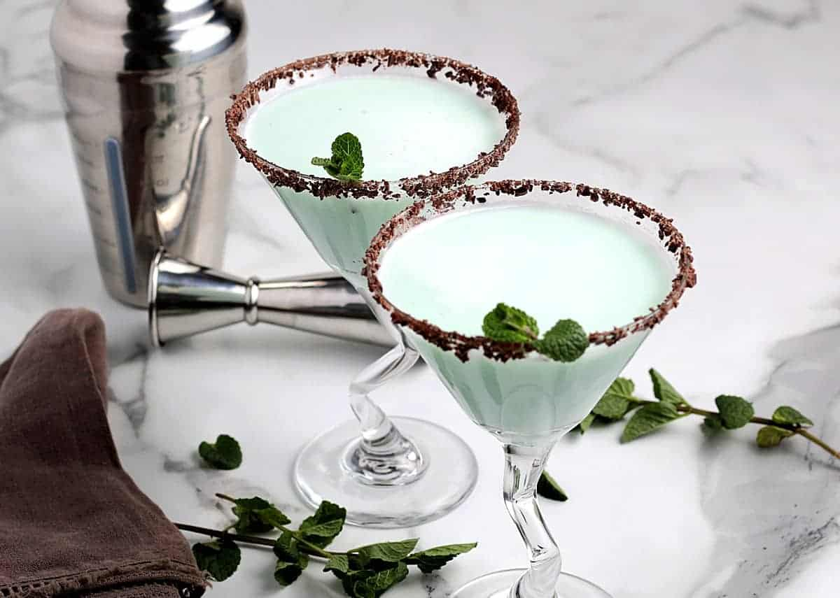 Wide photo of two martini glasses filled with a pale green and frothy cocktail.