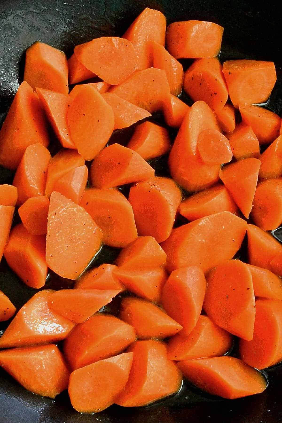 Overhead view of rolled cut carrots in a pan.