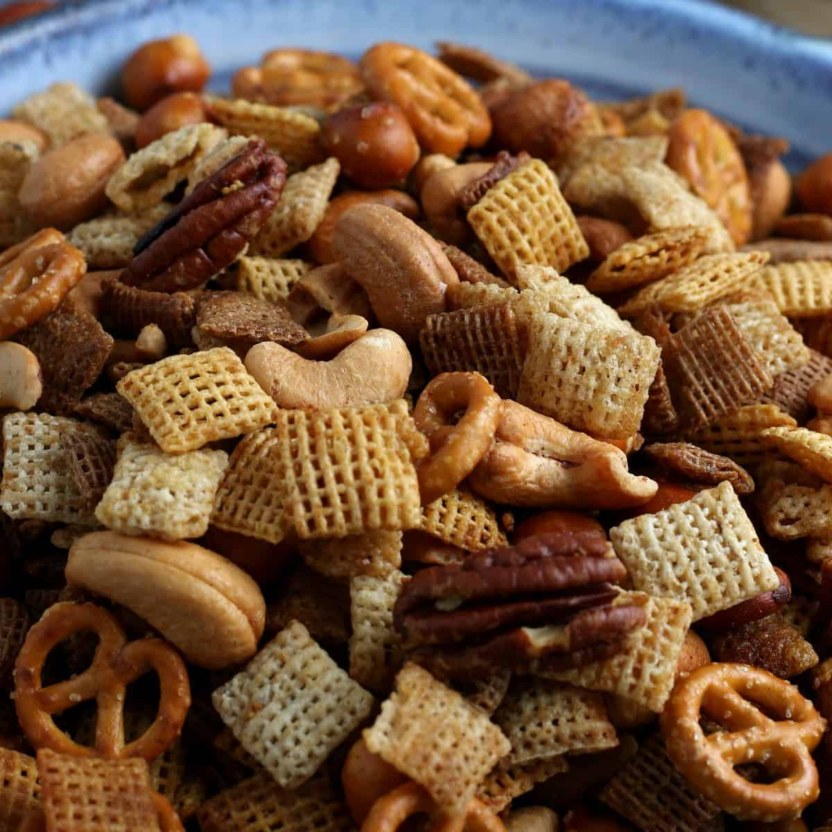 Close up of a snack mix with cereals, pretzels and nuts.