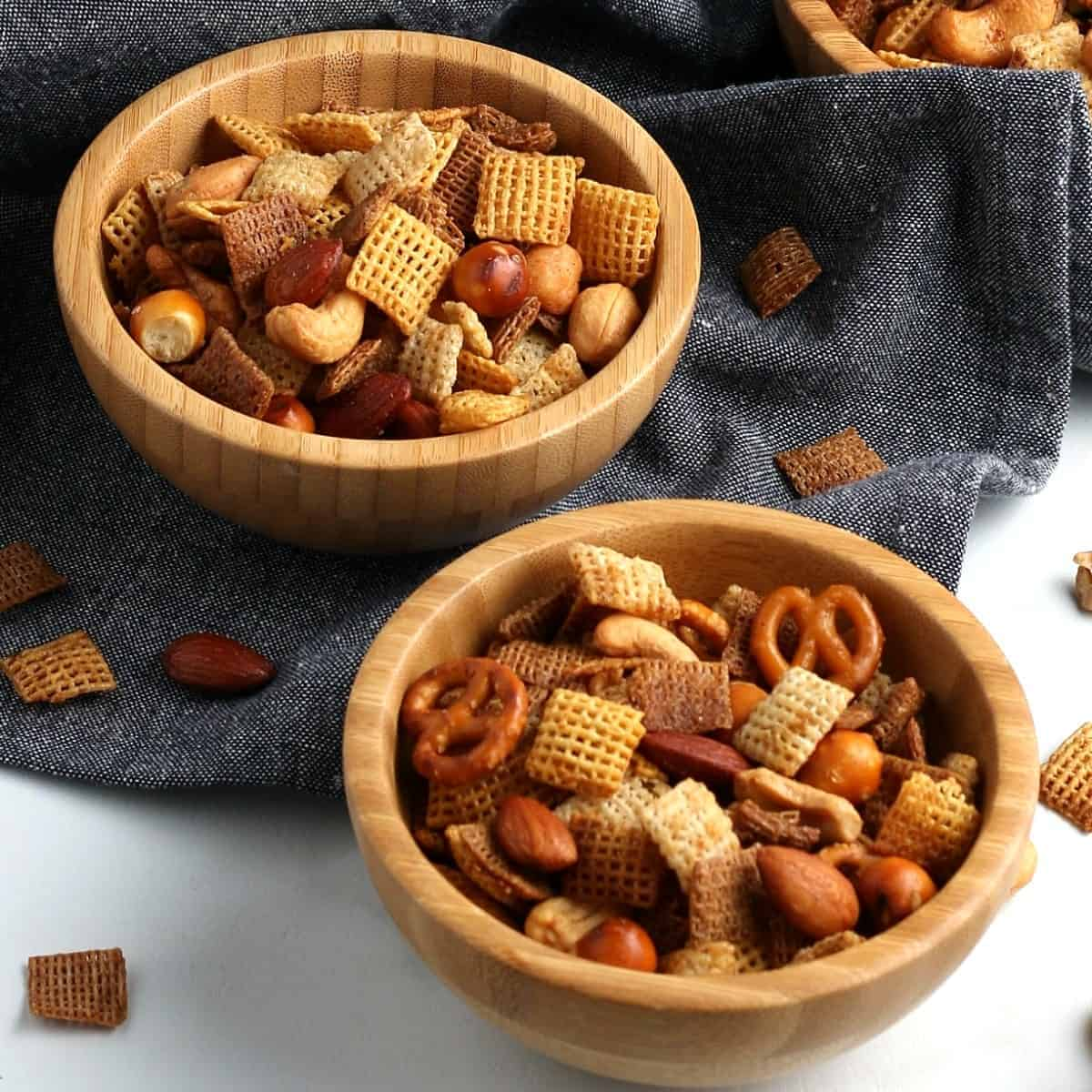 Two bowls full of a chex mix type of cereal and nuts.