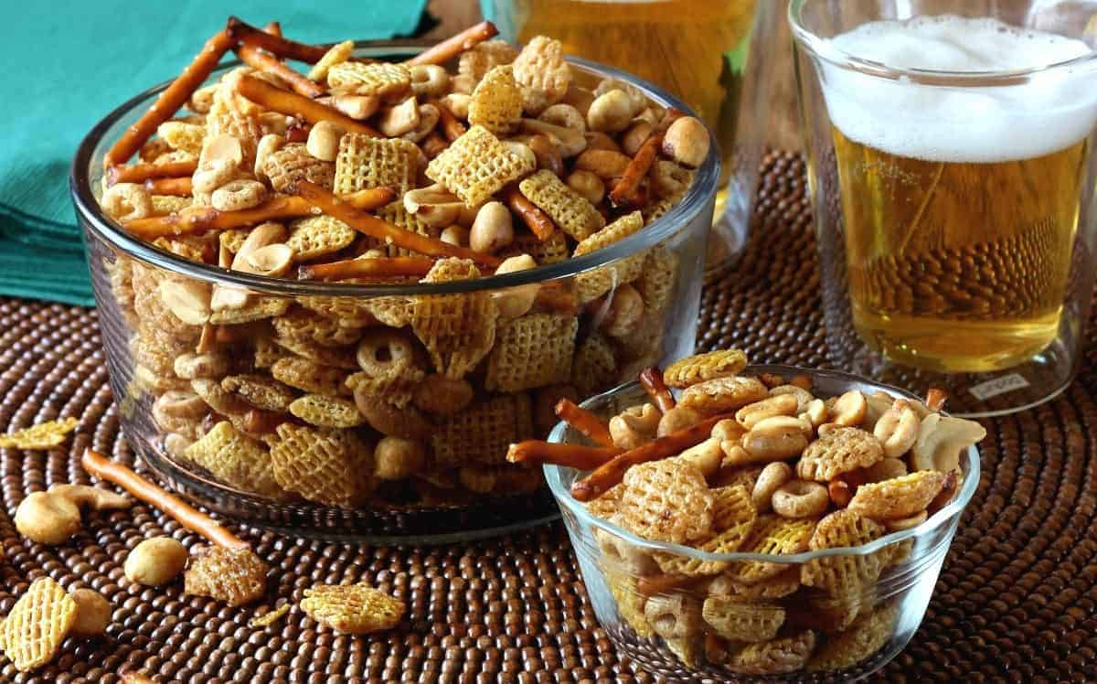 Glass serving bowl and individual bowl filled with snack mix.