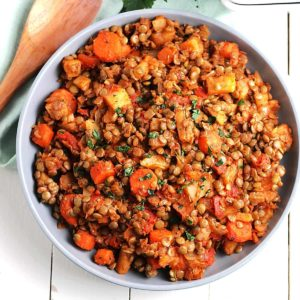 Overhead view of a serving dish full of potatoes, carrots and lentil hash.
