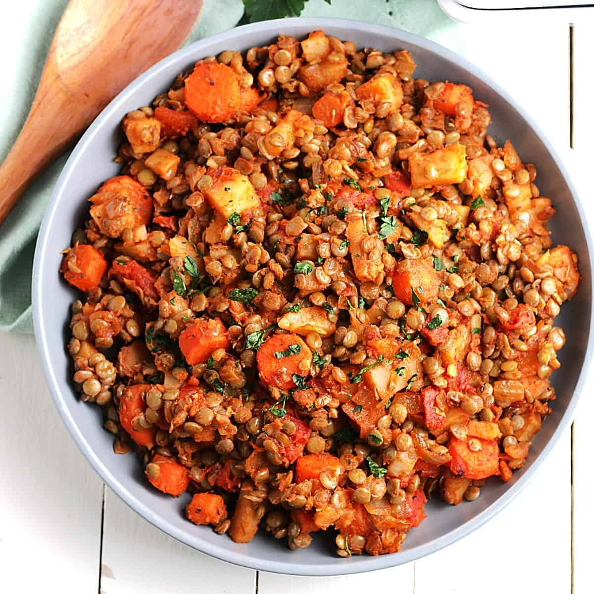 Overhead view of a serving dish full of a skillet potato recipe with carrots and lentils.