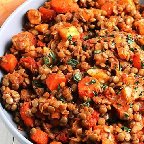 Cropped bowl full of skillet potatoes, lentils and carrots hash.