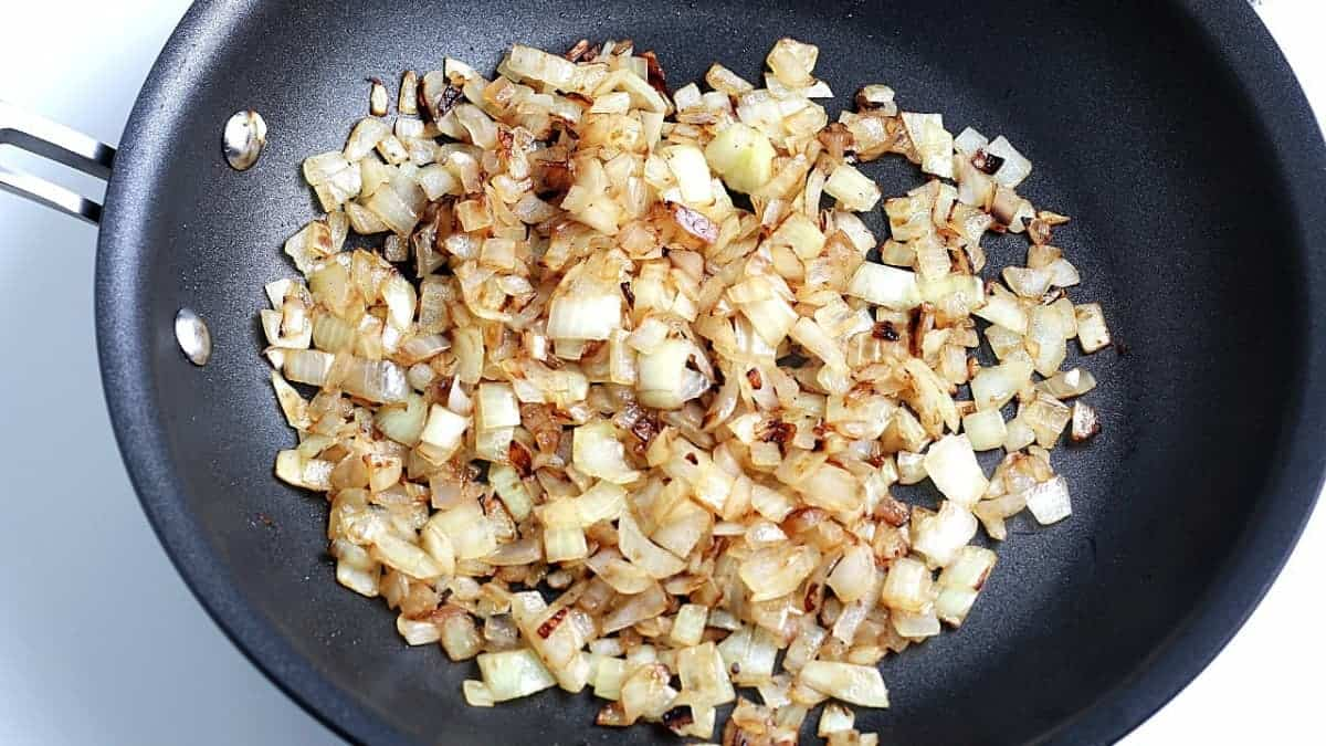 Overhead view of sauteed onions in a frying pan to start the vegan hash.