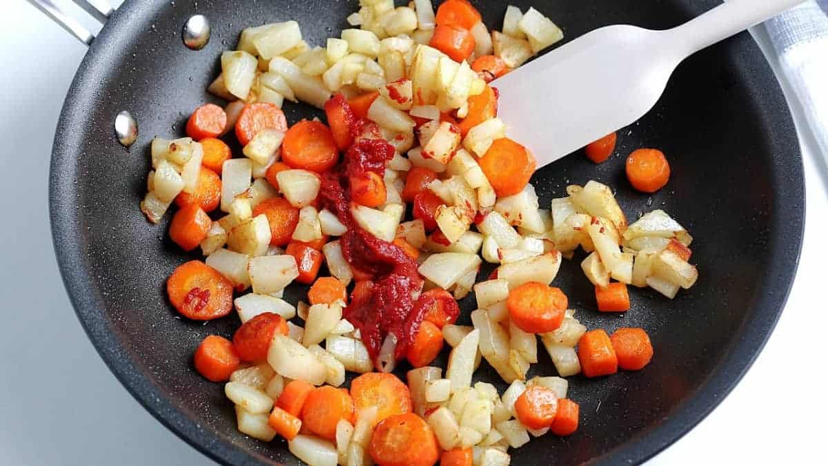 Skillet full of browned carrot and potatoes chunks with tomato paste being added.