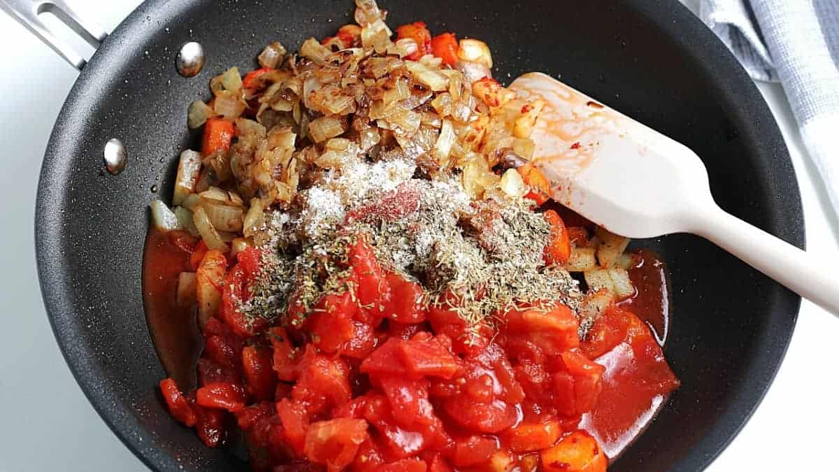 A skillet with added tomatoes, herbs and onions on top of the potatoes.