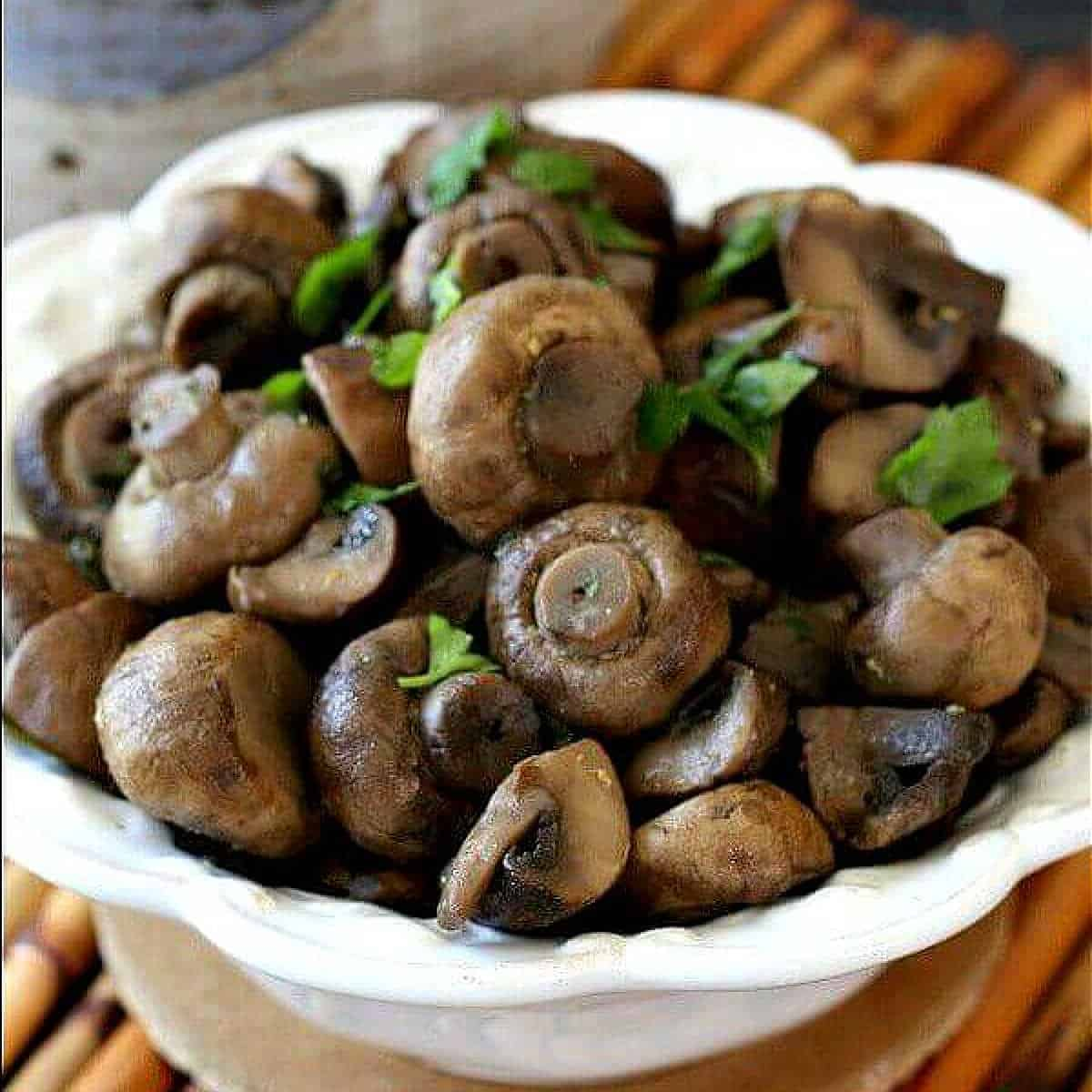 Tilted bowl filled with glistening marinated mushrooms