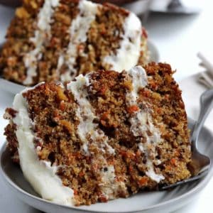 Two close up slices of cake filled with grated carrot with frosting on top.