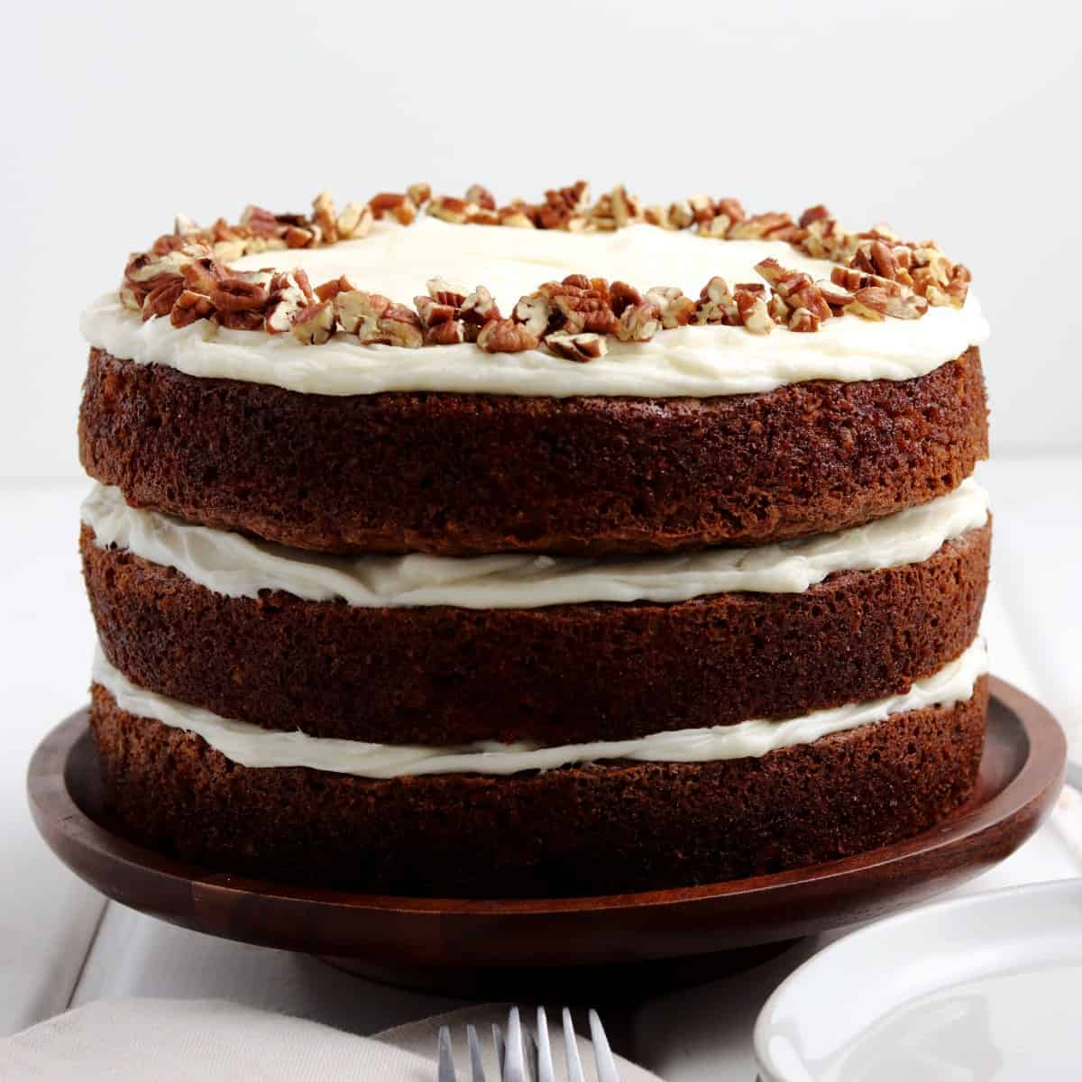 Straight on photo of three layers of carrot cake and layered with cream cheese frosting.