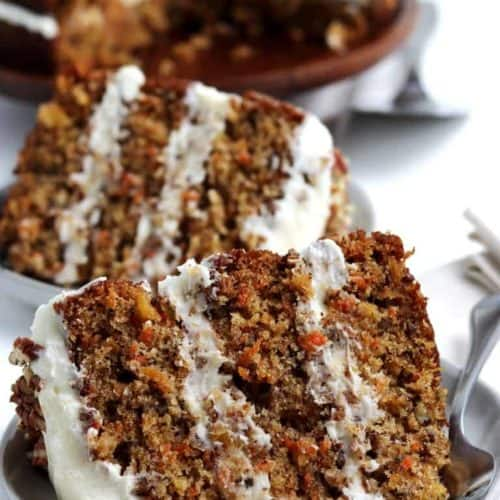 Two fat slices of a moist carrot cake showing carrots through the slices.