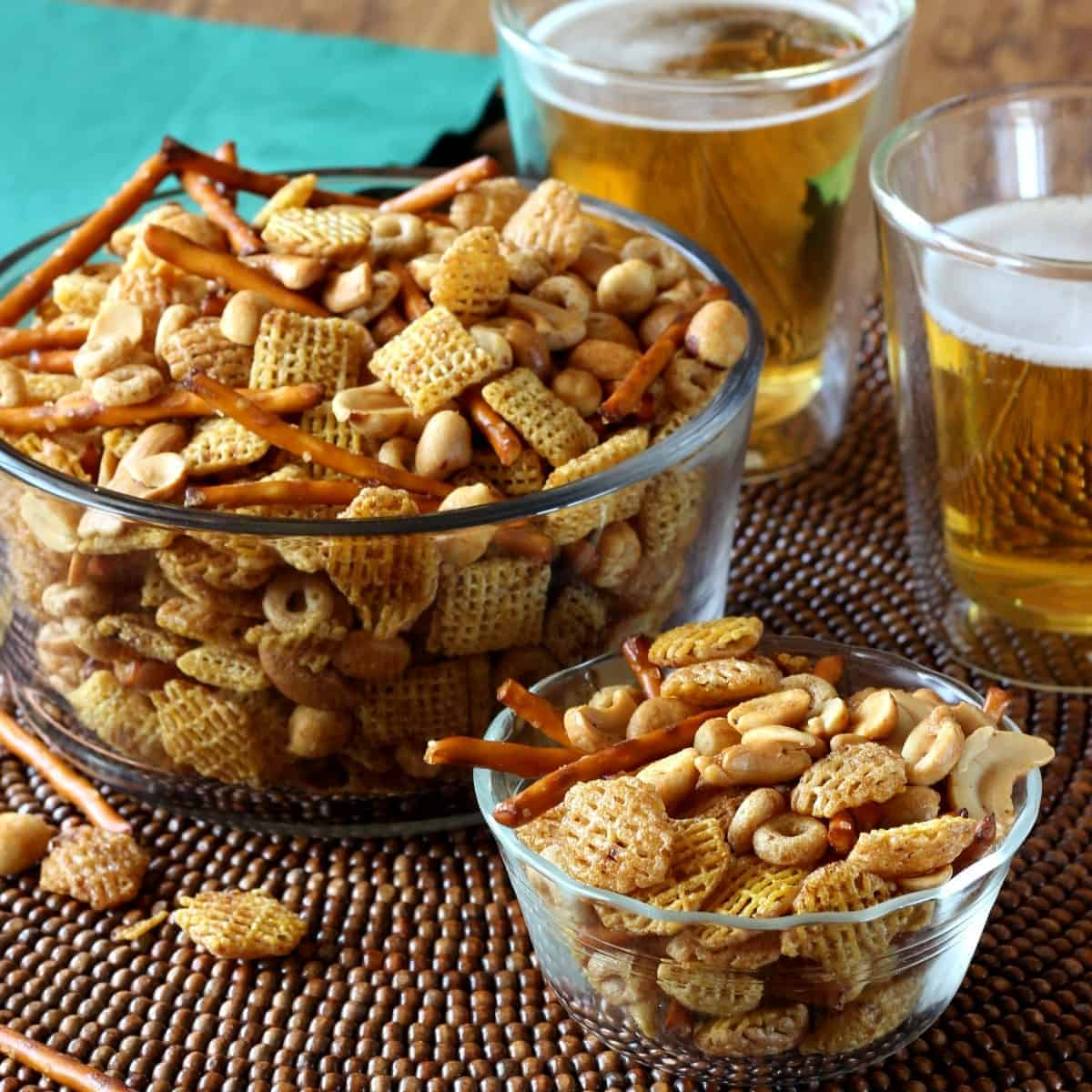 Two glass bowls filled with chex mix snack of cereal and nuts.