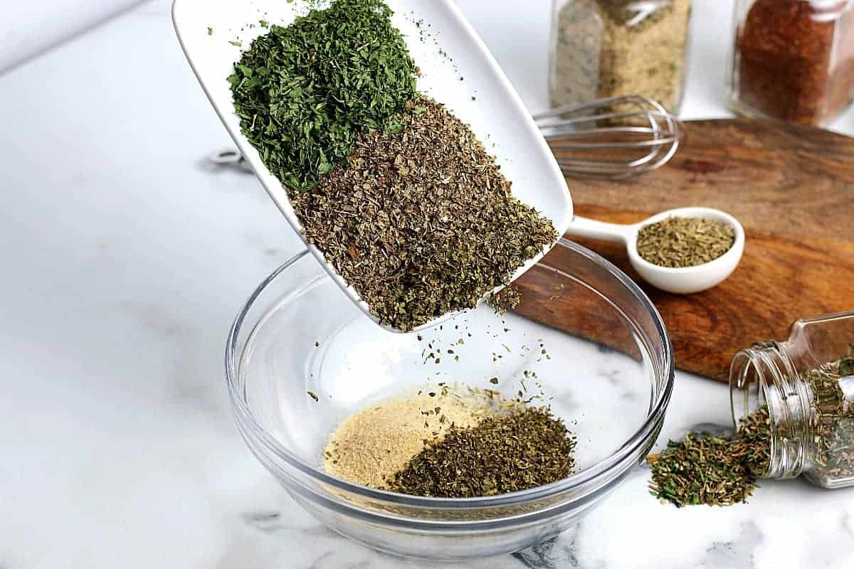 Adding green dried herbs to the Italian mixture.