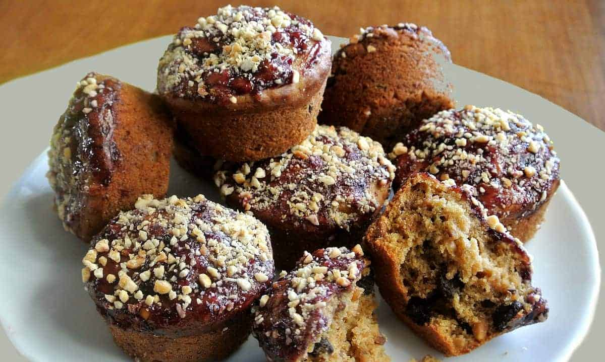 A pile of muffins with one broken open on a white plate.
