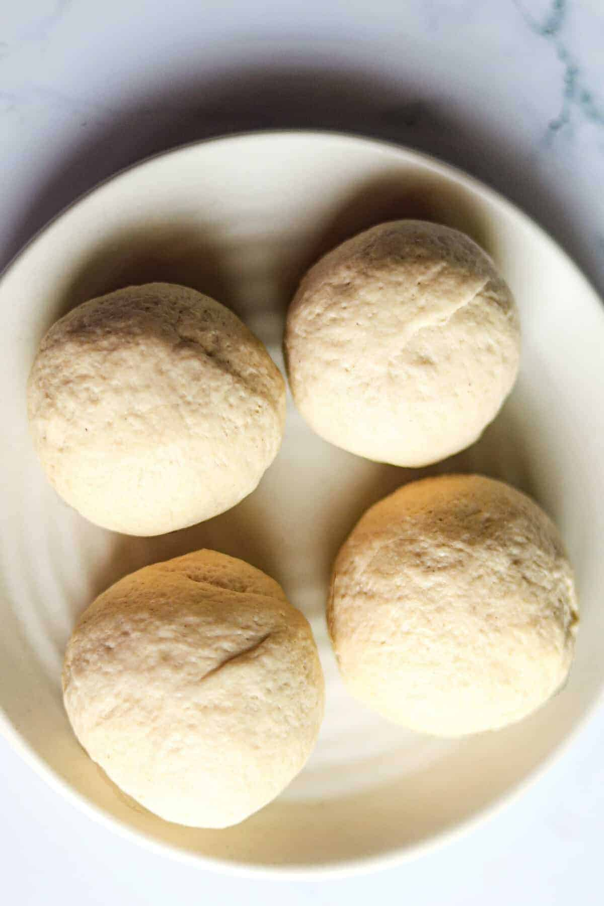 Four dough balls resting on a plate.