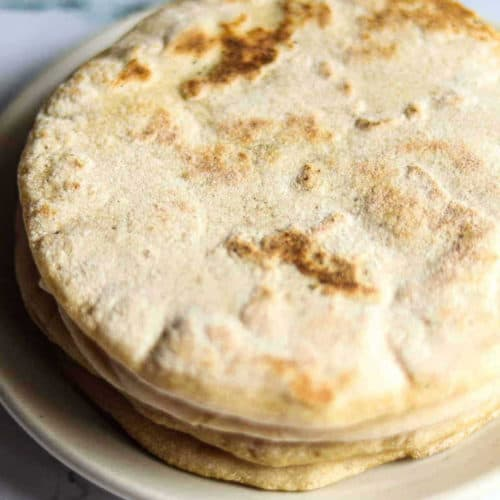 Stack of four baked pita bread rounds on a white plate and marble.