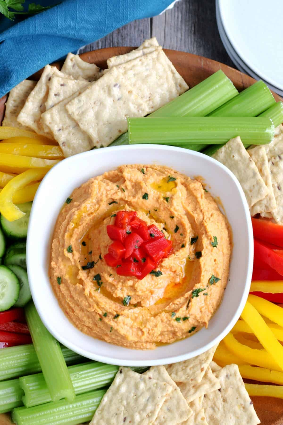 Overhead view of roasted red pepper hummus with veggies and crackers surrounding it.