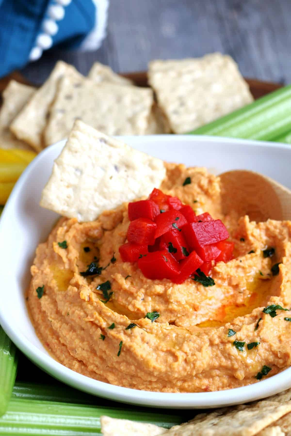 Extreme closeup photo of red bell hummus swirled with an olive oil drizzle.