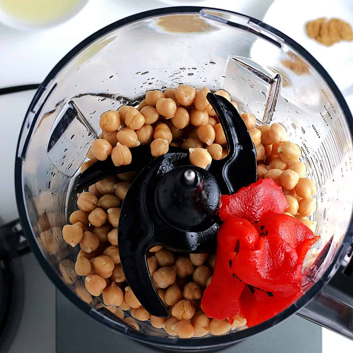 Overhead of chickpeas and red bell peppers in a food processor.
