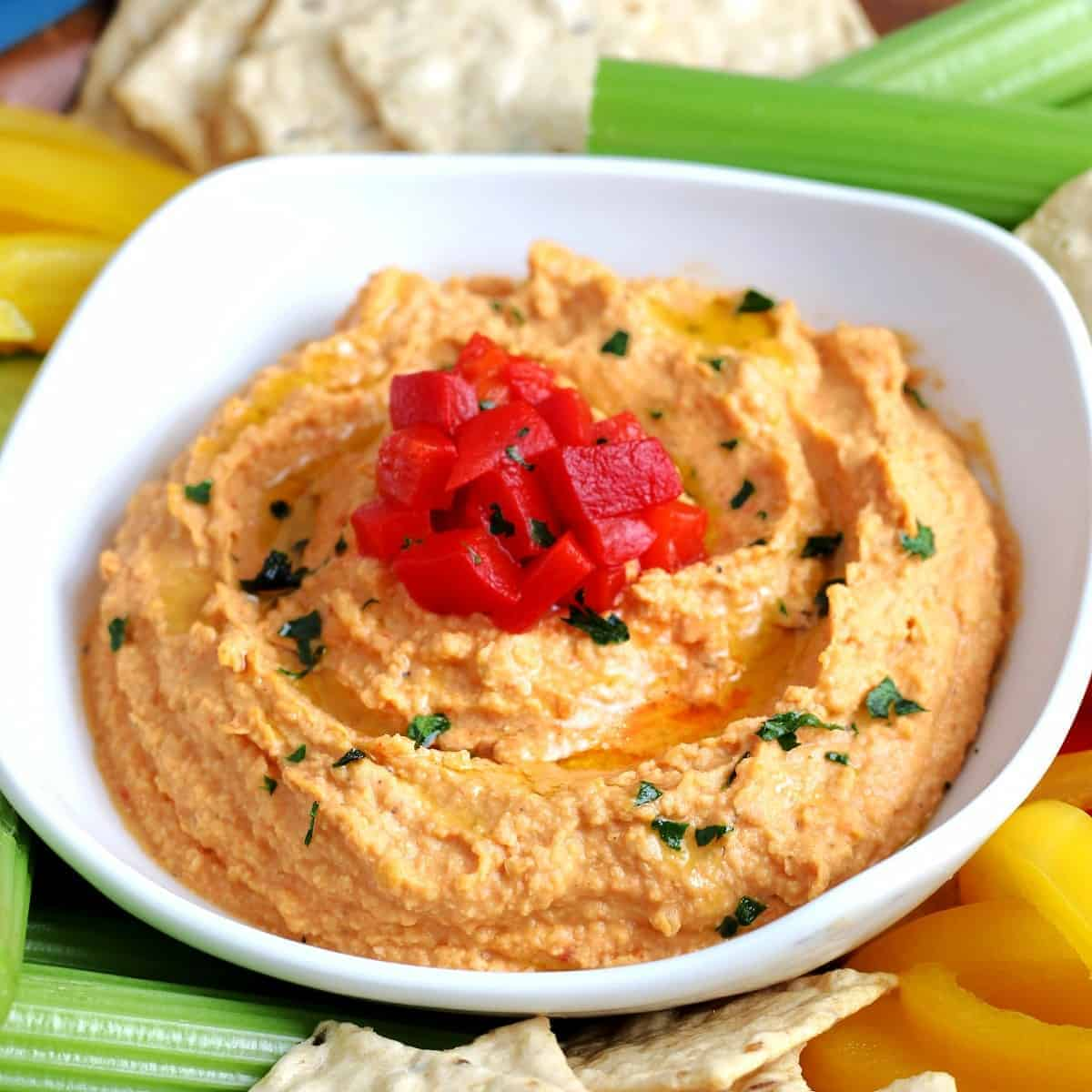 Tilted white bowl full of red pepper hummus with veggies around.