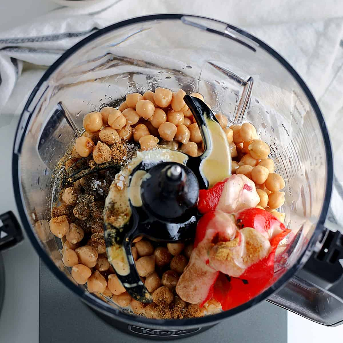 Overhead of a food processor filled with chickpeas, bells, tahini and seasoning.