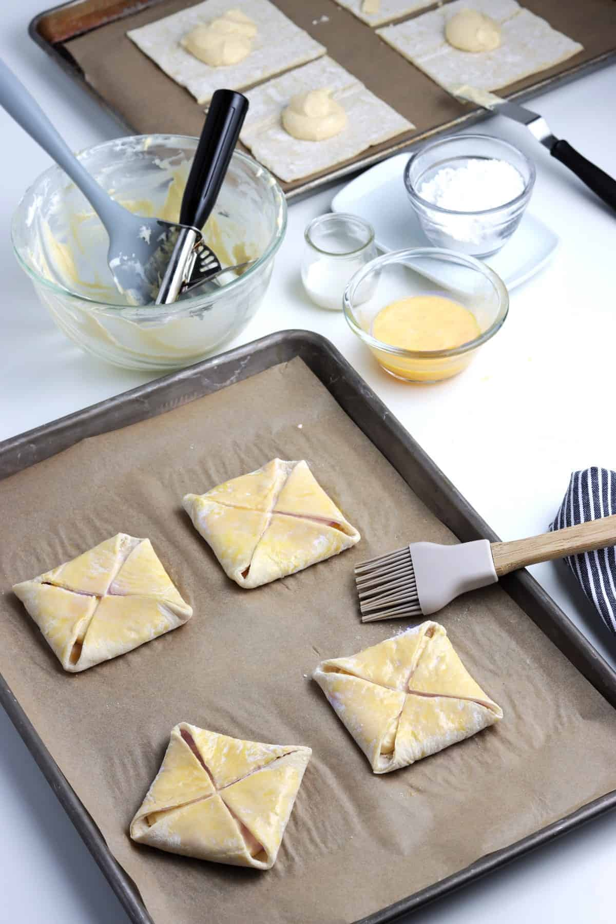 Brushing dairy free cream cheese filled puff pastry on a baking sheet.