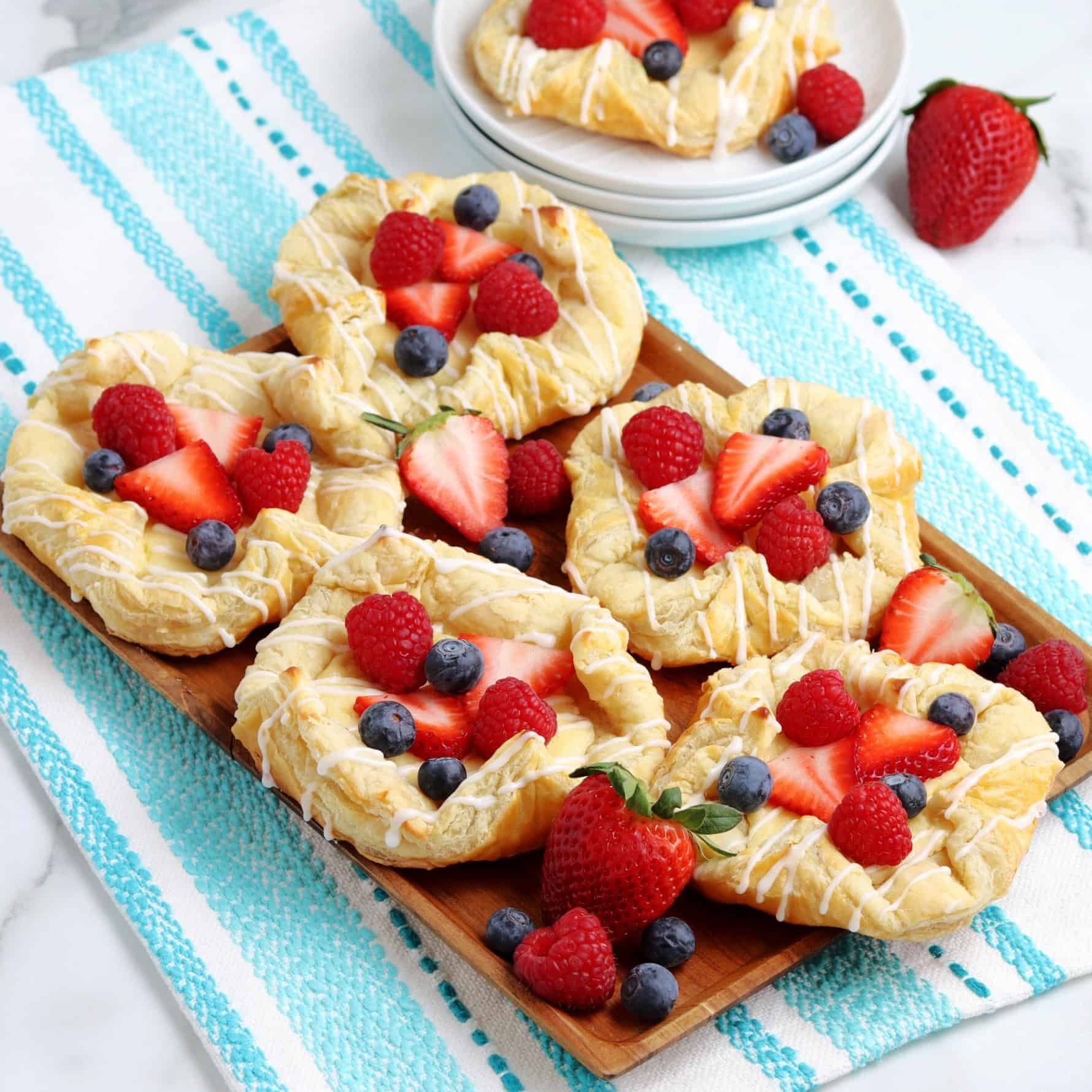 Angled wooden tray filled with berry topped pastries.
