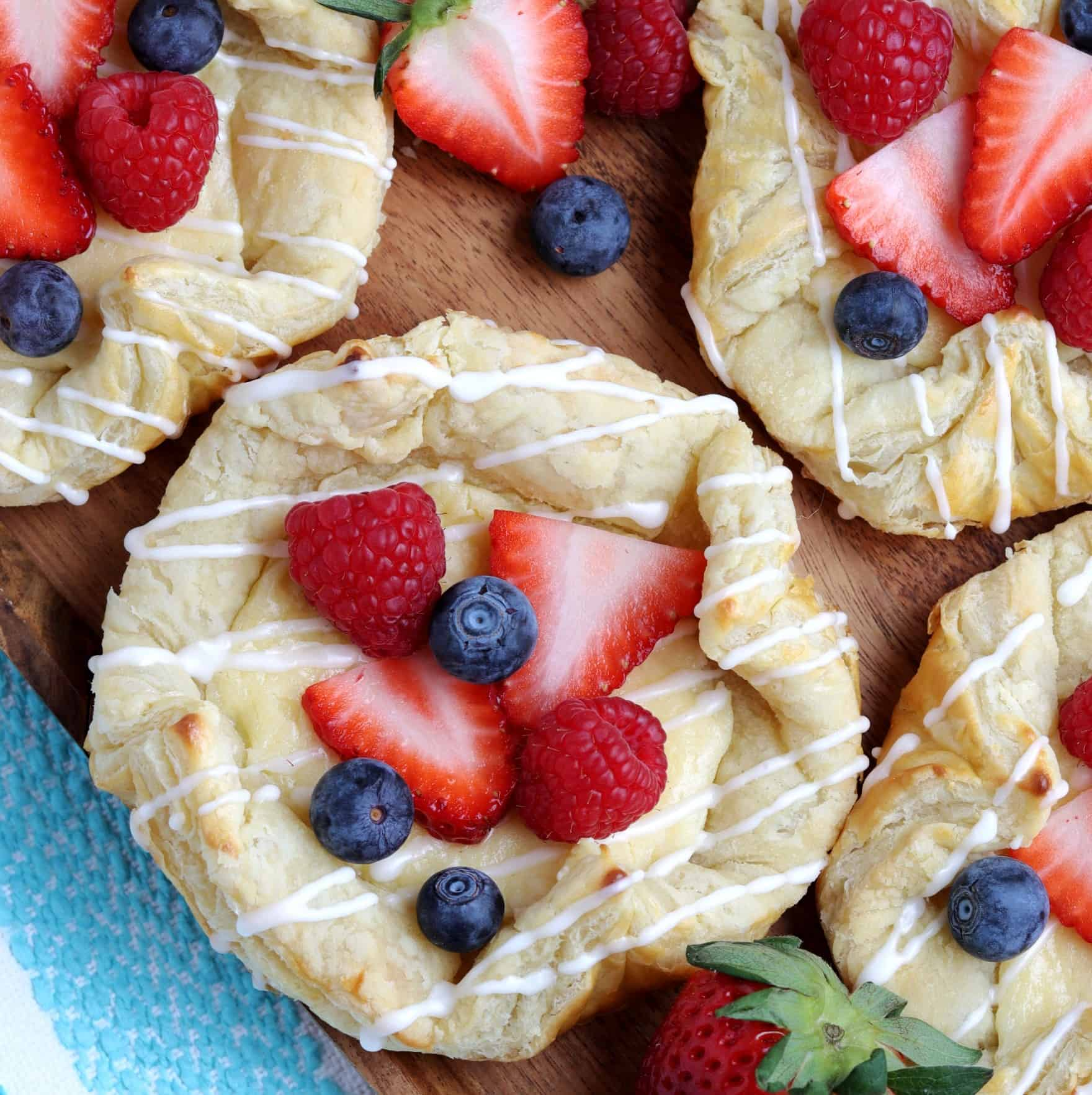 Centered Vegan Cream Cheese Danish drizzled with icing and berries.