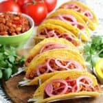 Six tacos lined up and ready to eat.