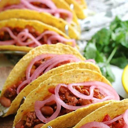 Lined up and filled sloppy joe tacos in a curve.