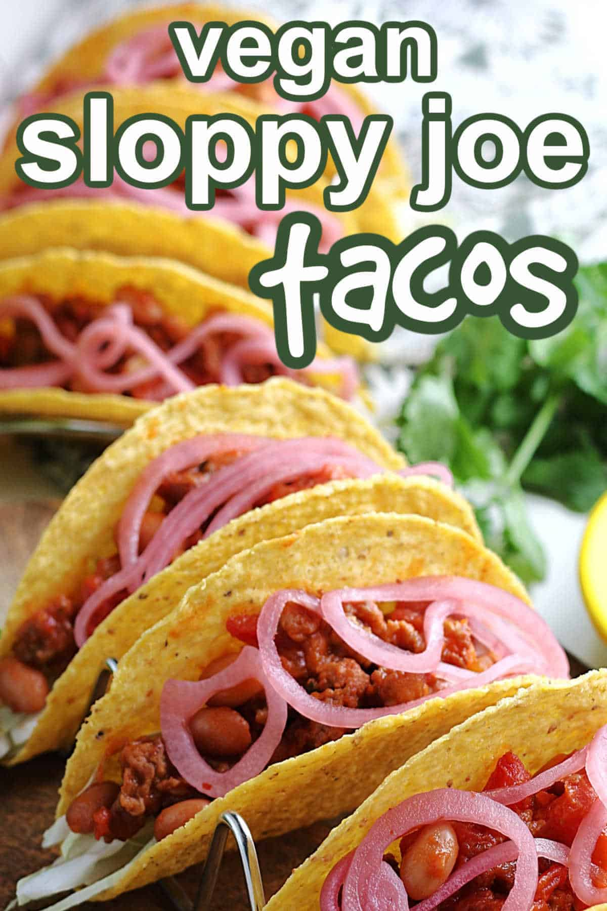 Lined up and filled sloppy joe tacos in a curve and up close.