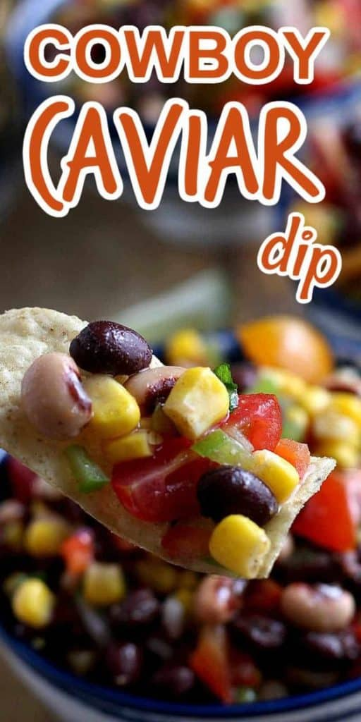 A tortilla chip loaded with veggie cowboy caviar dip being help close to the camera lens.