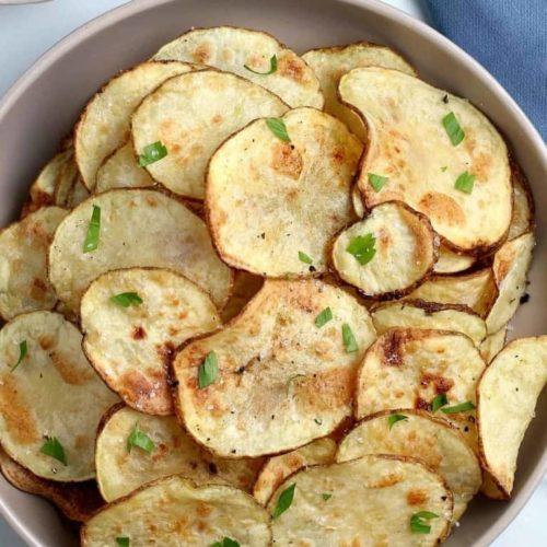 Overhead photo of golden potato chips in an air fryer.