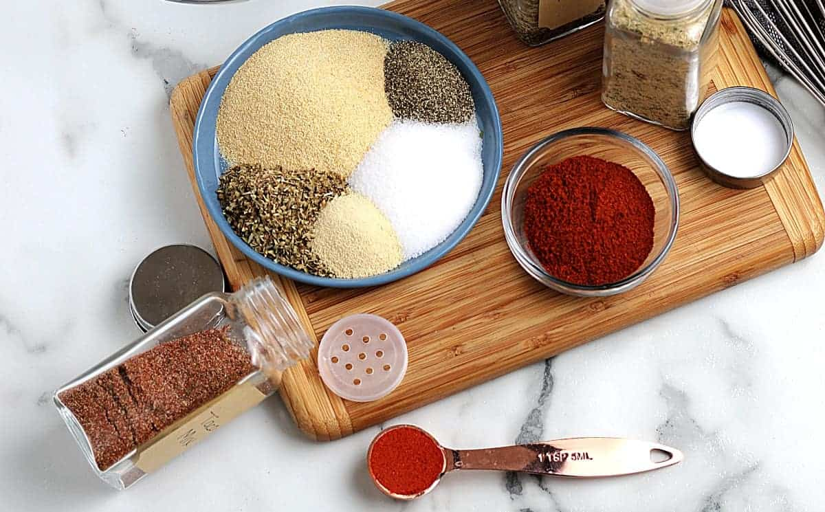 Ingredients for a spicy spice mixture all laid out on a wooden board.