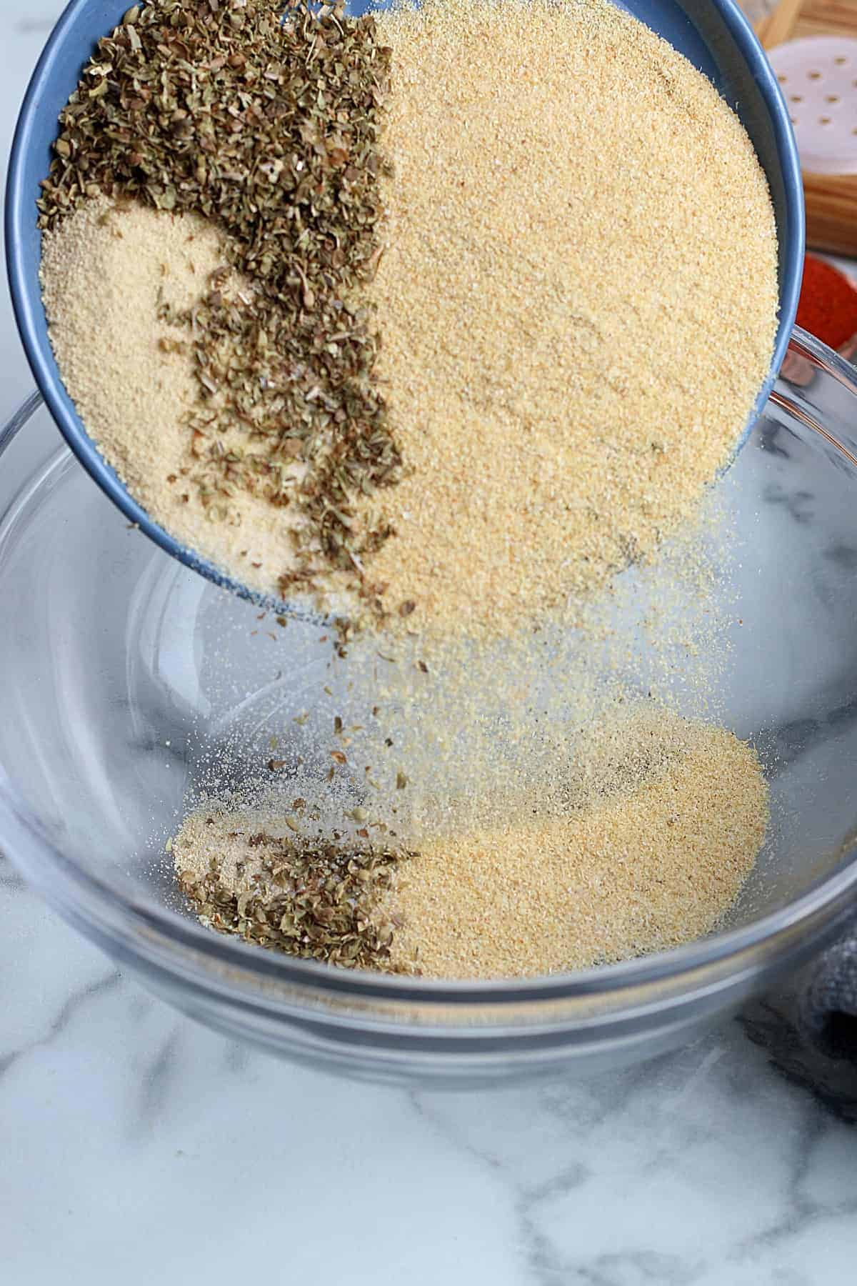 Pouring garlic, onion and oregano seasonings into a mixing bowl.