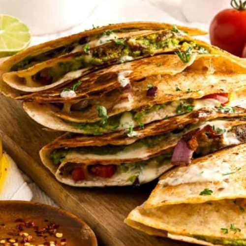 Stack of 4 vegan quesadillas showing the veggies inside.