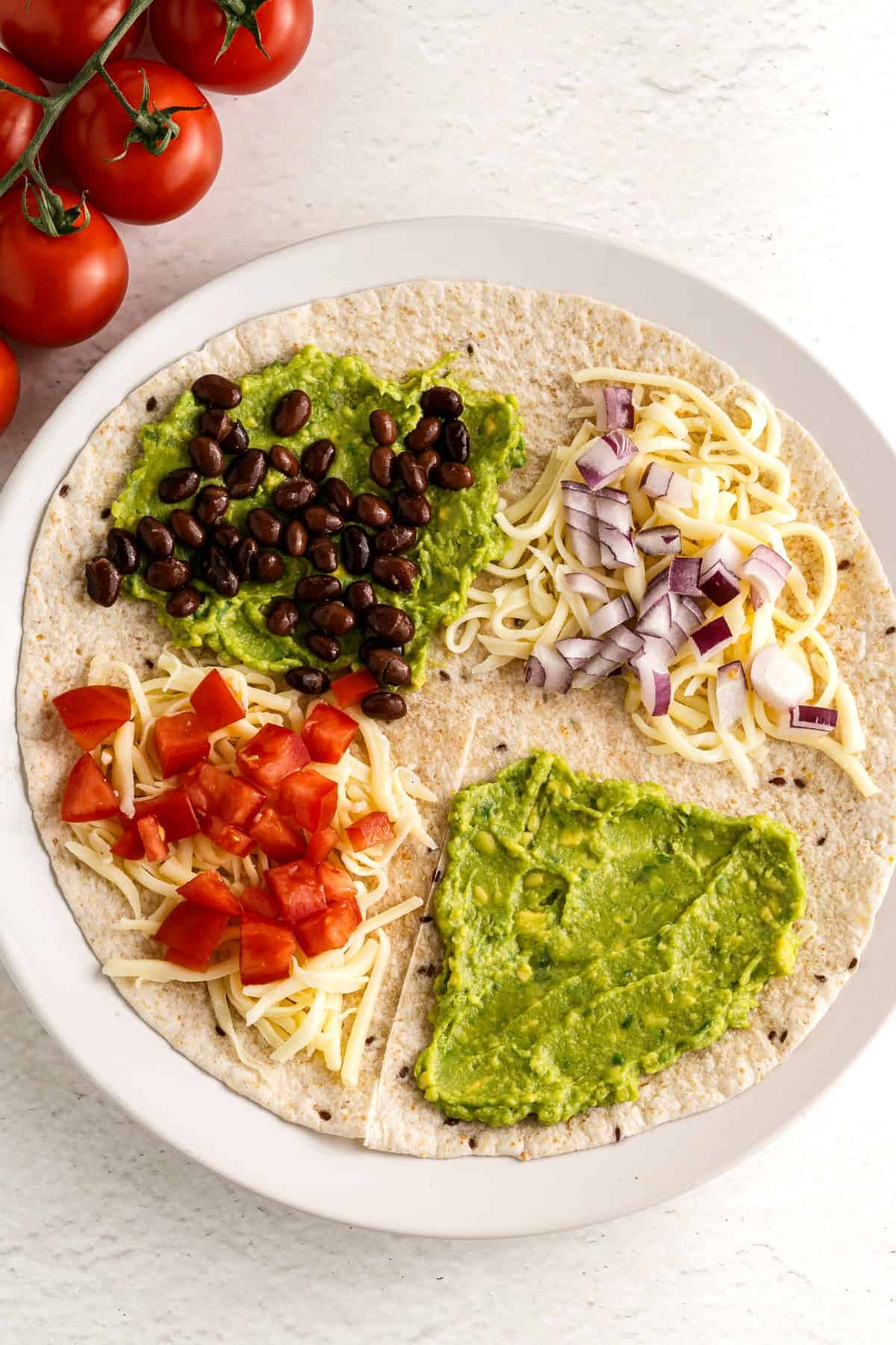 A tortilla filled with veggies and ready to be folded.