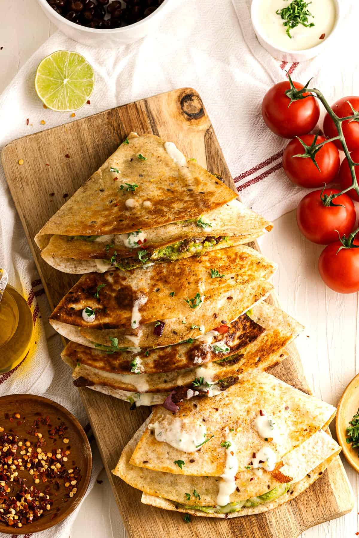 Overlapping folded and cooked tortilla sandwiches with vegan crema.