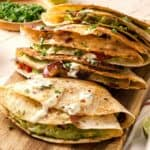 Four folded vegetarian quesadillas overlapping each other on a cutting board.