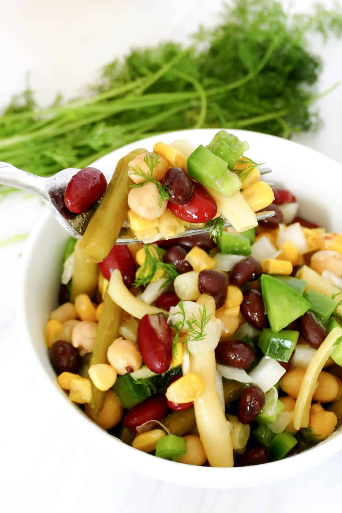 A forkful of bean salad is being help close to the camera lens.