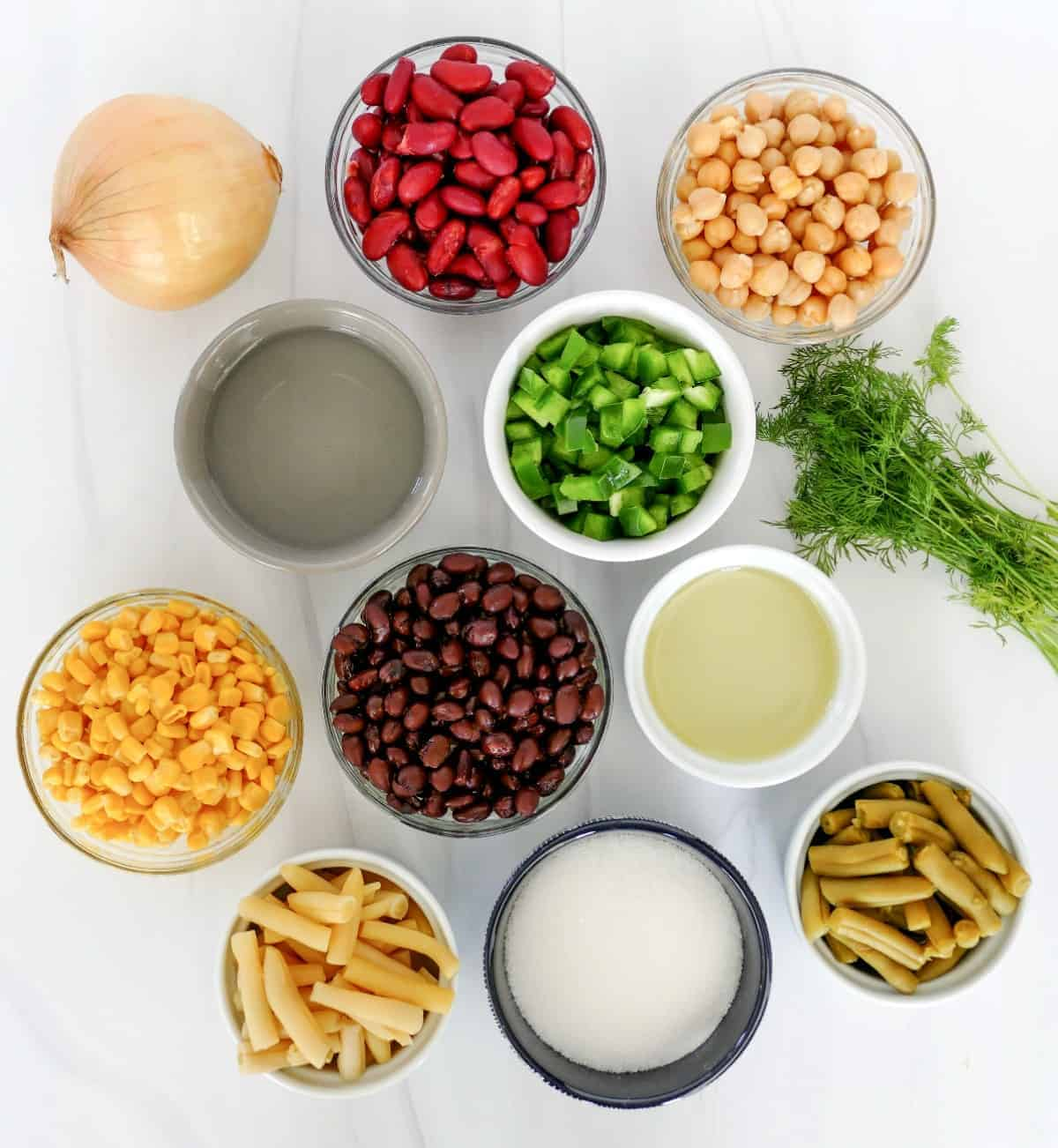 All of the ingredients for a five bean salad in individual bowls.